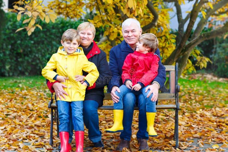 祖父、祖母和两个小孩男孩,坐在秋天的孙停放 库存图片