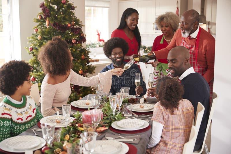 祖父倾吐的香槟在饭桌上在多一代时,混合的族种家庭圣诞节庆祝 库存图片