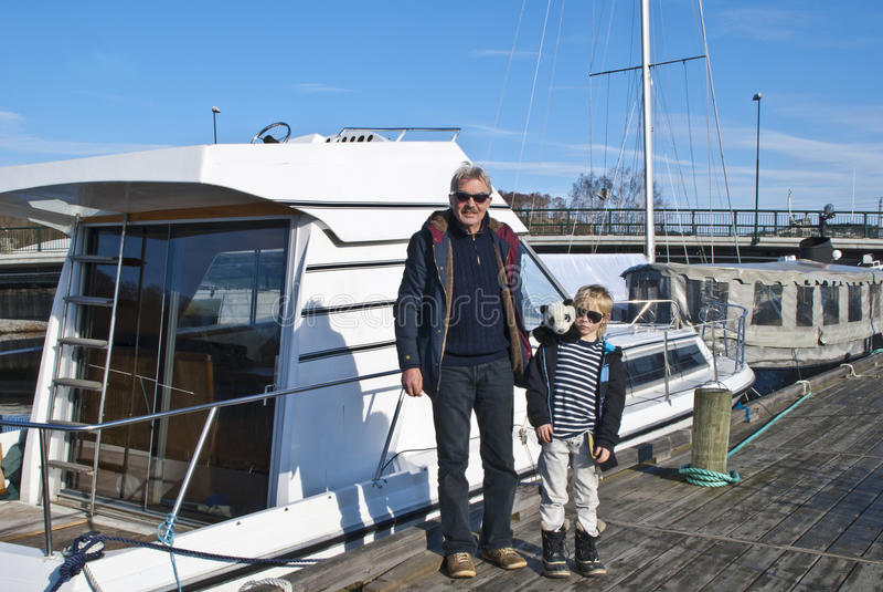 祖父和孙子检查了小船 免版税库存照片