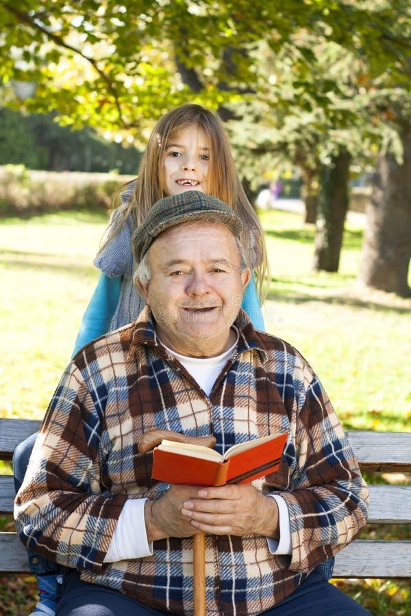 祖父和孙子阅读书 免版税库存图片