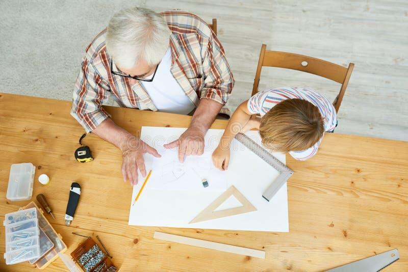 祖父和男孩图画鸟舍剪影 库存照片