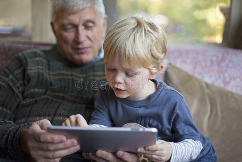 祖父孙子个人计算机片剂使用 免版税图库摄影