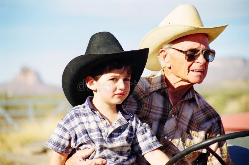祖父孙子极大的拖拉机 免版税库存照片