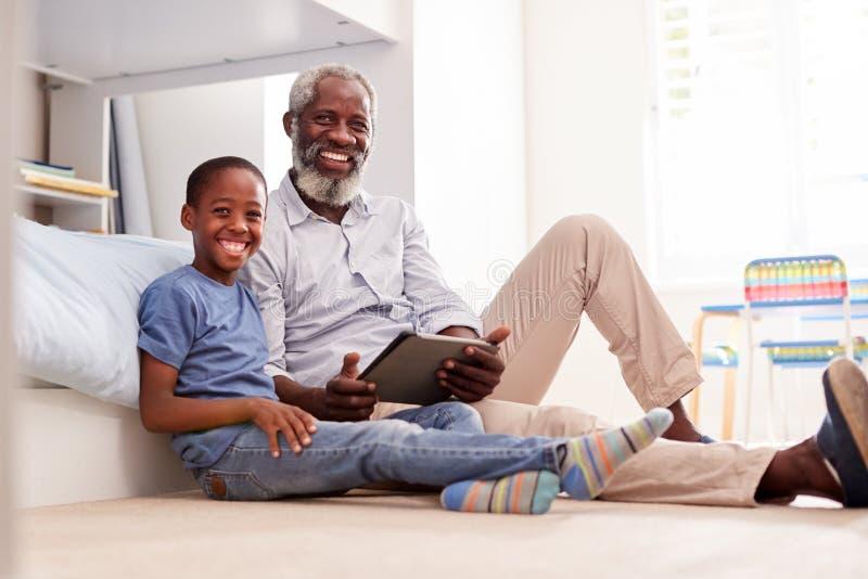 祖父开会画象与孙子的在使用一起数字片剂的柴尔兹卧室 免版税库存照片