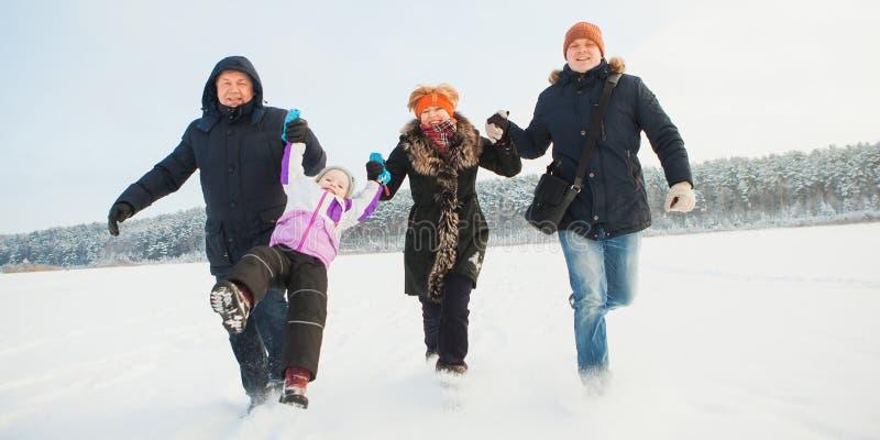 祖父母、父亲和女儿、愉快的家庭举行胳膊和奔跑一起 库存图片