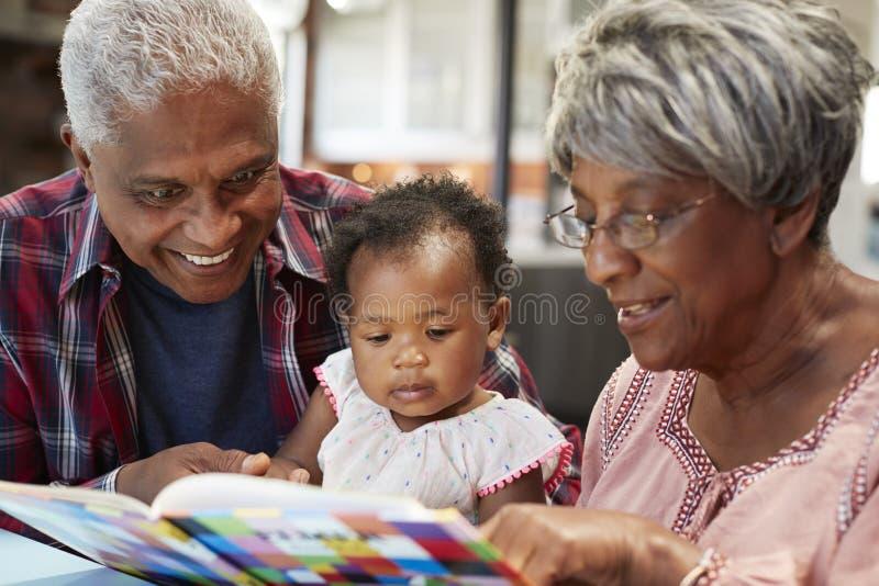 祖父母与小孙女的阅读书在家 免版税库存照片