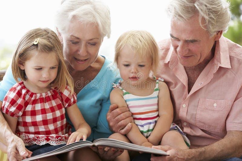 祖父母和孙在车顶上的座位的阅读书 免版税库存图片