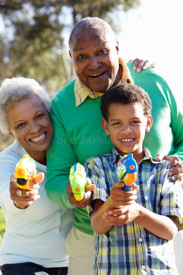 祖父母和孙子射击水枪 库存图片