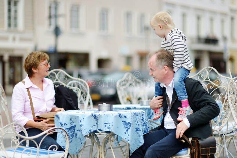祖父母和他们的孙室外咖啡馆的 库存照片