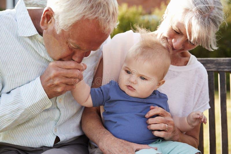 祖父母坐位子在有小孙子的庭院里 免版税库存图片