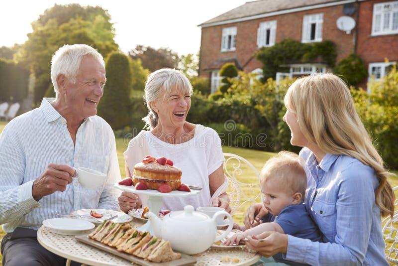 祖父母食用与孙子和成人女儿的下午茶 免版税库存图片