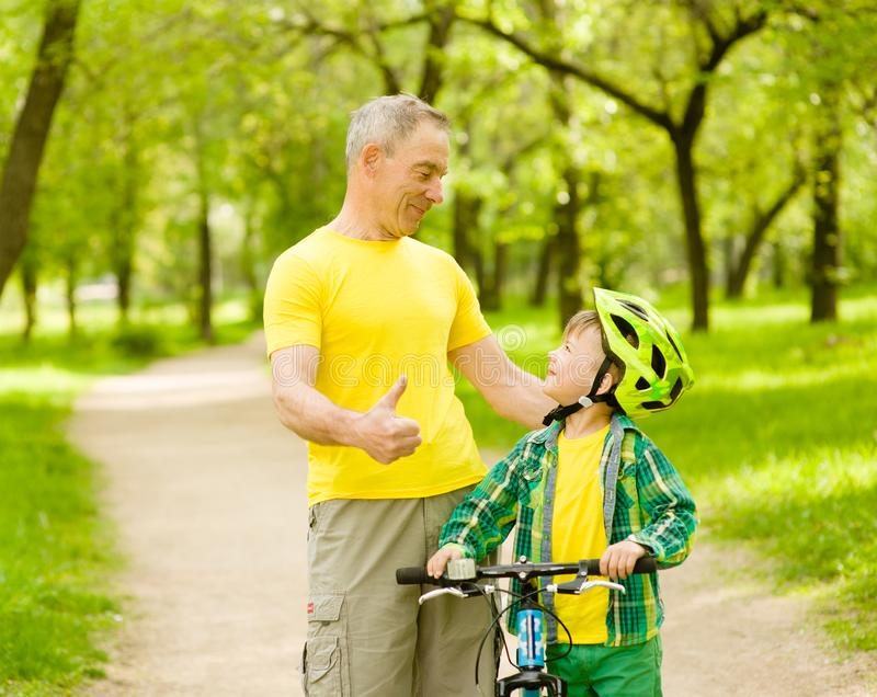 祖父谈话与他的骑自行车和显示赞许的孙子 图库摄影