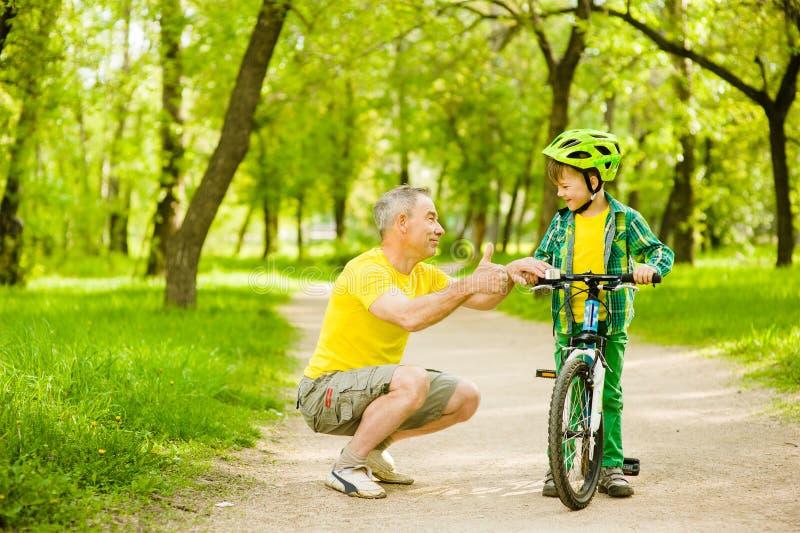 祖父谈话与他的骑自行车和显示赞许的孙子 库存照片