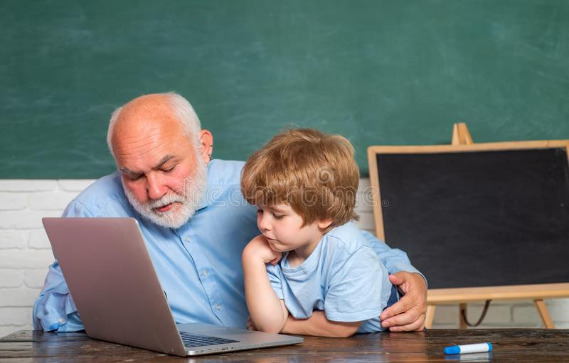 祖父谈话与孙子 教育和教学的概念 使用计算机的老师和男小学生在类  免版税库存图片