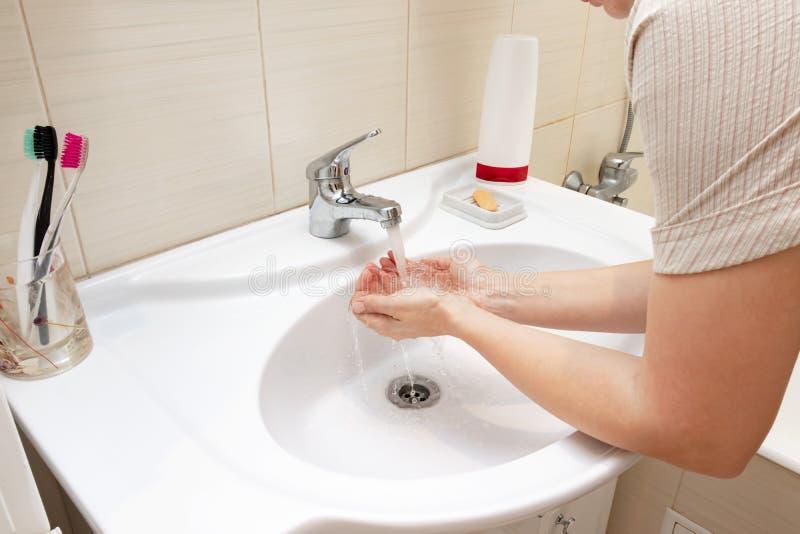 祝愿手用在卫生间水槽的水的妇女 Desease预防和卫生学概念 有用,好习性 免版税库存图片