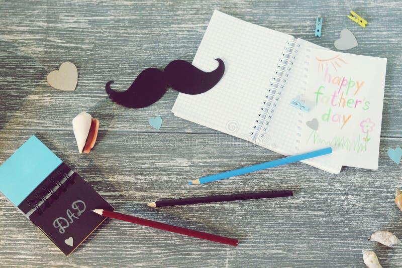 祝贺在父亲节,笔记薄,指南针,纸髭,在木桌上的海洋装饰 库存照片