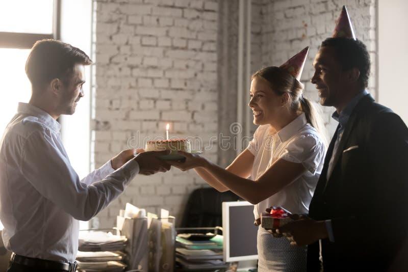 祝贺工友的不同的同事与给与蜡烛的生日蛋糕 库存图片