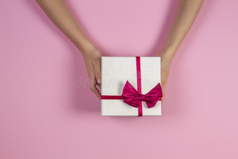 祝贺背景 拿着有丝带的孩子手当前礼物盒在桃红色背景 顶视图 礼物为 免版税库存照片