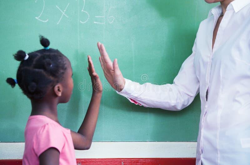 祝贺与算术的美国黑人的女学生的老师 免版税库存图片