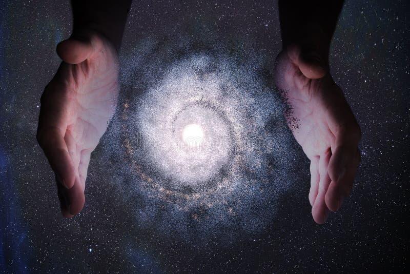 神创论概念 上帝之手在创造宇宙中的银河 库存图片