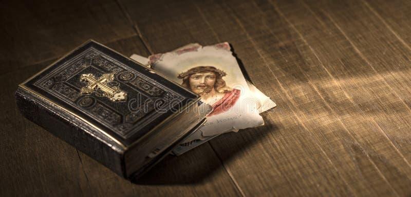 神圣的圣经和圣洁卡片与耶稣基督图象在书桌上 库存图片