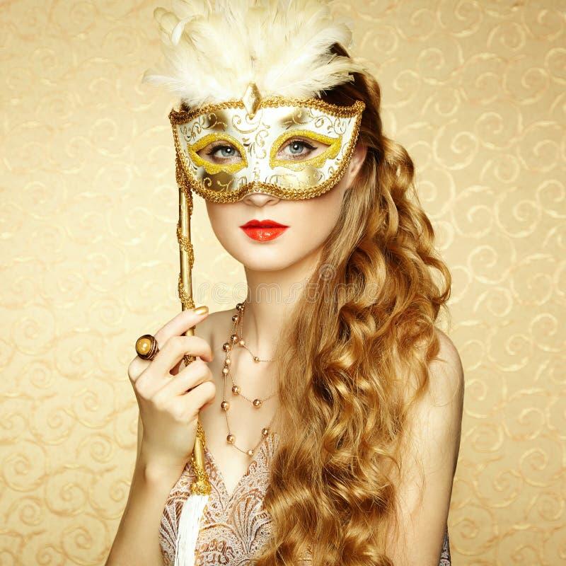 神奇金黄威尼斯式面具的美丽的少妇 免版税图库摄影