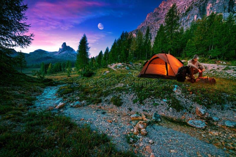 神秘的夜风景,在前景远足、营火和帐篷 库存图片
