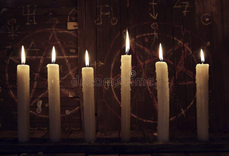 神秘主义者接近与灼烧的蜡烛反对与五角星形的木背景 免版税图库摄影
