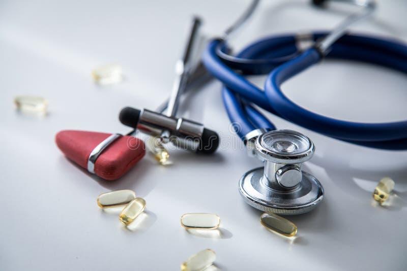 神经学家有听诊器、大型装配架和Tylor反射锤子和医疗药片的医生办公室疗法的 库存照片