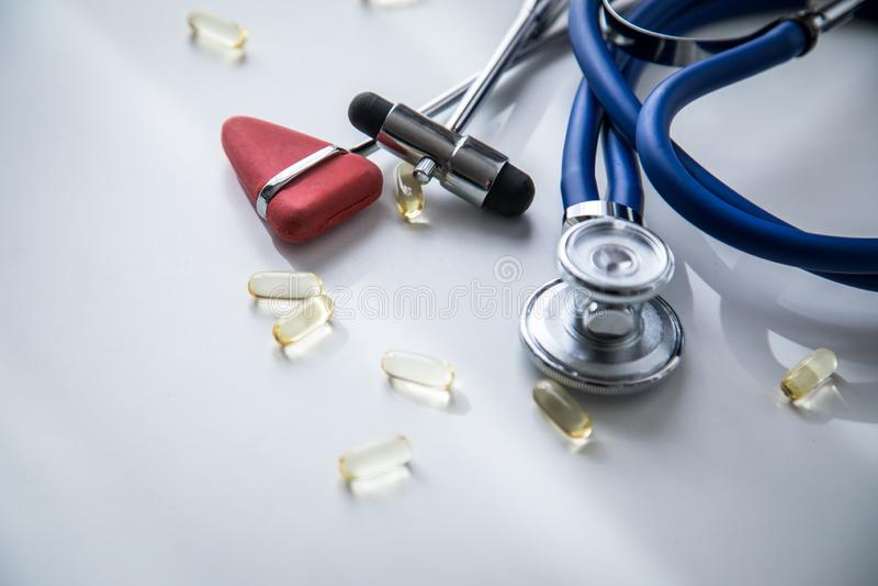 神经学家有听诊器、大型装配架和Tylor反射锤子和医疗药片的医生办公室疗法的 免版税库存照片