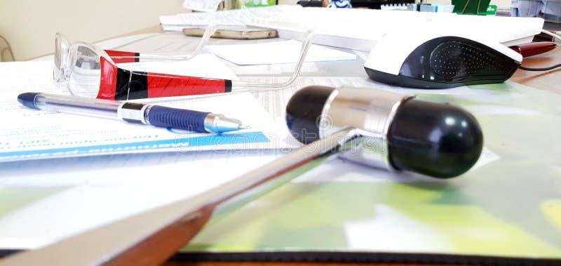 神经学锤子、笔、玻璃和任命在桌上在医生 图库摄影