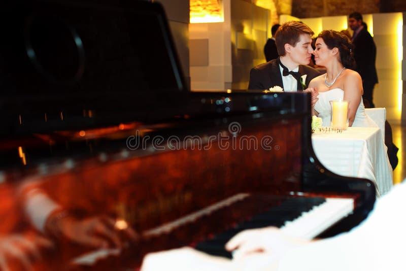 神色从在迷人的婚礼夫妇的一架钢琴的后面 免版税库存图片