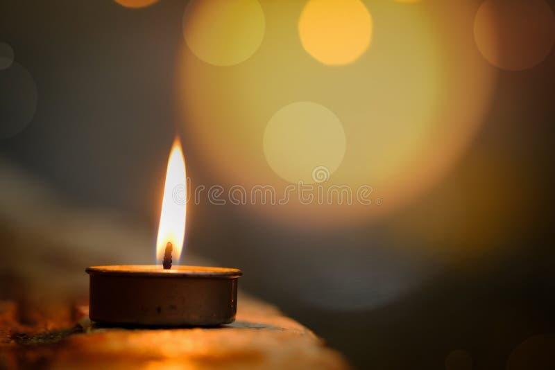 祷告和希望概念 烛光焰光在与abstrac的晚上 免版税库存图片