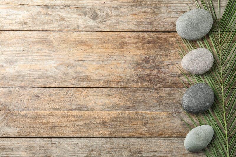 禅宗石头和热带叶子在木背景 免版税图库摄影