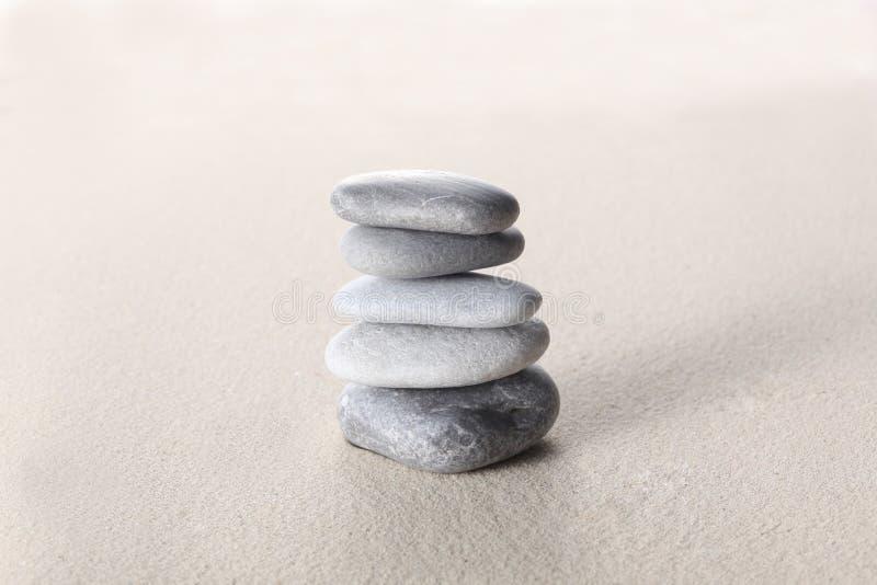 禅宗石头概念,灰色石头在与拷贝空间的沙子堆了您的文本的 库存图片