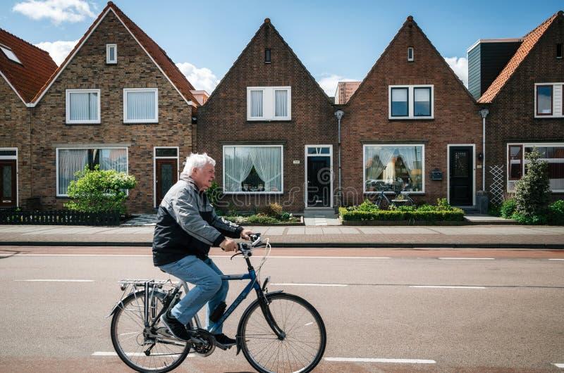 福伦丹村庄的村民乘在典型的传统房子前面的自行车,荷兰 库存图片