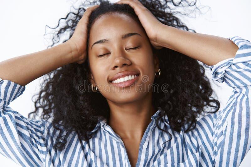福利放松概念 接触卷发的可爱的轻松的愉快的无忧无虑的深色皮肤的年轻千福年的妇女 免版税库存图片