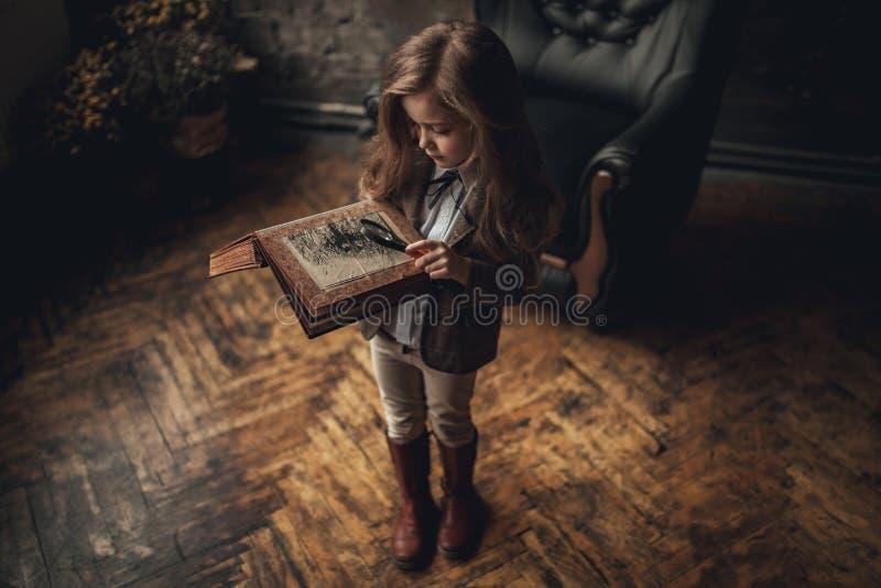 福尔摩斯的图象的儿童女孩在屋子里站立并且看与放大器的photoalbum在老内部背景  特写镜头 库存图片