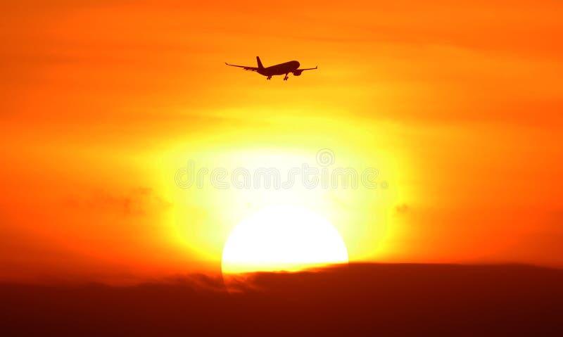 离去飞机的剪影到达在日落期间热带天堂巴厘岛印度尼西亚 库存照片