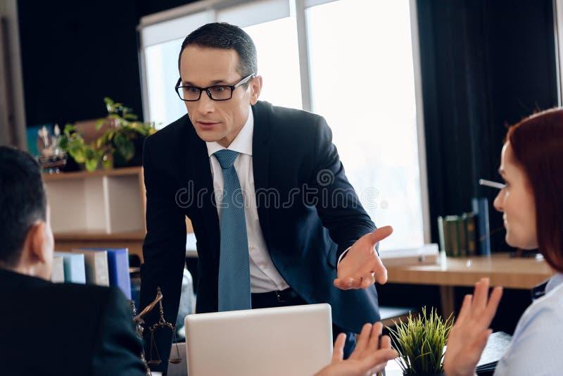 离婚律师把手指向红头发人妇女在坐在办公室的人旁边 回到视图 免版税库存照片