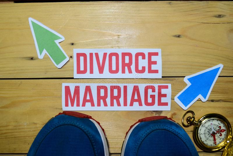 离婚或婚姻与运动鞋和指南针的反方向方向标在木 库存照片