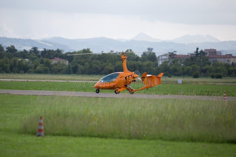 离开从跑道的小和淡桔色的直升机 库存图片
