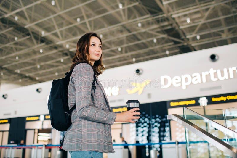 离开区域的旅客女孩在机场 免版税库存照片