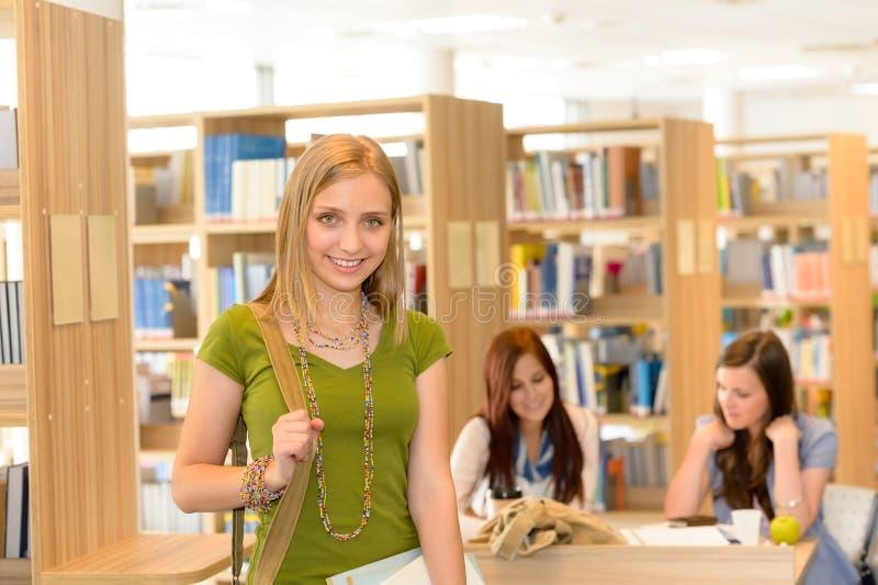 离开图书馆高中的微笑的学员女孩 库存图片