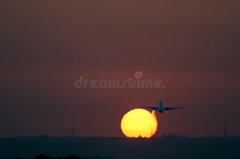 离开在塞维利亚机场的飞机在与黄色太阳和红色天空的日落 库存图片