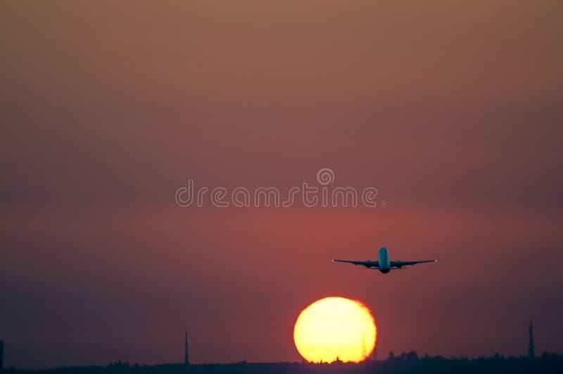 离开在塞维利亚机场的飞机在与黄色太阳的日落 库存图片
