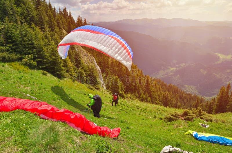 离开在壮观的山风景前面的滑翔伞 库存图片