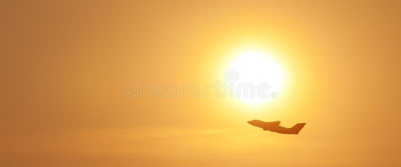 离开在日落的商业飞机剪影 库存图片