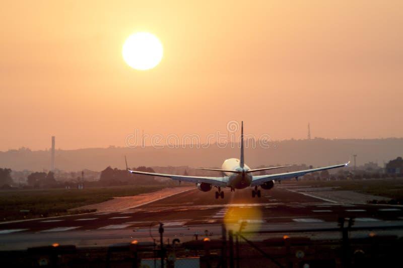 离开在机场的飞机在日落 免版税库存照片