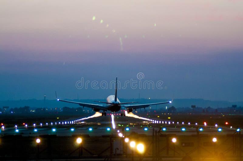 离开在机场的飞机在晚上 免版税图库摄影